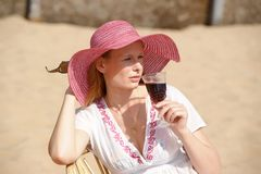 Blonde in a chaise longue on the beach wearing a hat. With a glass of wine royalty free stock photos