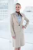 Blonde cheerful businesswoman standing hand on hips Royalty Free Stock Image