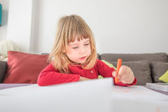 Blonde child drawing on white paper Royalty Free Stock Image