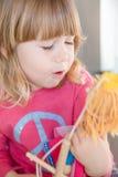 Blonde child pink shirt talking to puppet Royalty Free Stock Image