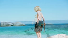 Blonde child playing with a wooden stick stock footage