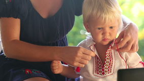 Blonde child in vyshyvanka watching cartoon stock video