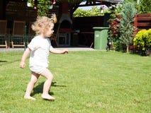 Blonde child walking. On grass Royalty Free Stock Image