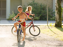 Blonde children ride bycicle under sunlight Stock Photo
