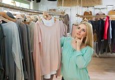 Blonde choosing new blouse Royalty Free Stock Image
