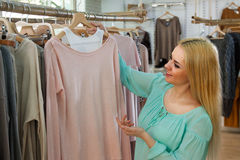 Blonde choosing new blouse Stock Image