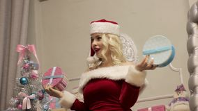 Blonde christmas girl posing for a photo. woman dressed as Santa standing in front of camera stock video footage