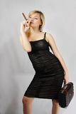 Blonde with cigar and valise Stock Photo