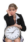 Blonde with clock looking bored. Blonde woman with clock looking bored Royalty Free Stock Photo