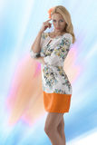 Blonde clothing dress with floral pattern abd finger near the te Stock Image
