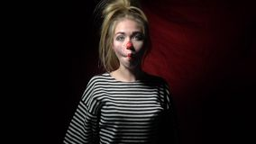 Blonde clown with a red nose cheerfully grimaces stock video