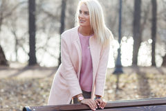 Blonde in coat at bench Royalty Free Stock Photography