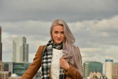 Blonde in coat on skyscraper roof royalty free stock photo