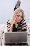 Blonde with computer near lake Stock Images