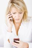 Blonde con dos teléfonos móviles Foto de archivo
