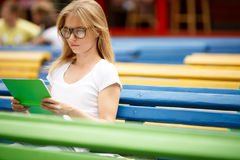 Blonde con el libro de lectura de los vidrios entre los bancos Imagenes de archivo