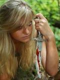 Blonde con la daga en sangre fotografía de archivo