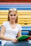 Blonde con la tableta que se sienta en banco de parque Foto de archivo