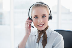 Blonde content businesswoman wearing a headset Stock Photos