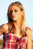 Blonde Country Girl. A beautiful blonde woman in a red plaid shirt Royalty Free Stock Photography
