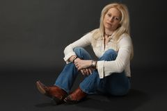 Blonde with cowboy boots sitting Royalty Free Stock Photography