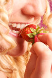 Blonde curly girl biting strawberry. Studio shot Stock Photos