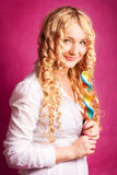 Blonde curly girl holding lollipop. Blonde curly smiling girl holding lollipop on the pink background royalty free stock photography