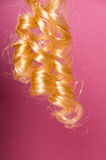 Blonde curly hair. With pink background Stock Photo