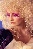 Blonde with curly hair. Girl like a doll with curly blond hair and extravagant make-up on the blue background Stock Photography