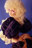 Blonde with curly hair. Girl like a doll with curly blond hair and extravagant make-up on the blue background Royalty Free Stock Photo