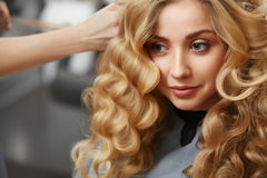 Blonde curly hair. Hairdresser doing hairstyle for young woman i Stock Photos