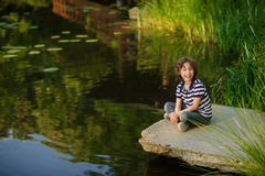 Blonde curly-haired boy sitting on the edge of the pond stock photos