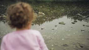 Blonde curly little girl throw stones in the river. Mountains background. Pink sweater stock video footage