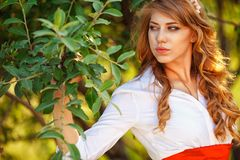 Blonde curly woman standing under the tree Royalty Free Stock Photography