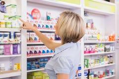 Blonde customer pointing medicine from shelf Stock Photos