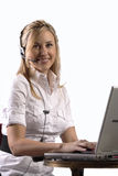 Blonde customer service girl working on laptop Stock Photos