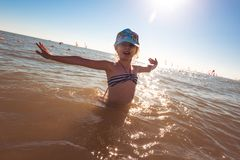 Blonde cute seven-year-old girl having fun and having a good time at the sea during the holidays.  stock images