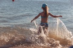 Blonde cute seven-year-old girl having fun and having a good time at the sea during the holidays.  royalty free stock image