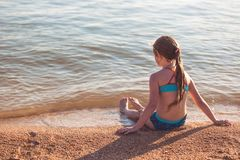 Blonde cute seven year old girl sitting on the beach during vacation.  royalty free stock photos