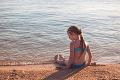 Blonde cute seven year old girl sitting on the beach during vacation.  stock photos