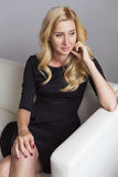 Blonde cute slim fit business woman in black dress sitting on a Stock Images