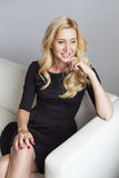 Blonde cute slim fit business woman in black dress sitting on a Royalty Free Stock Photography