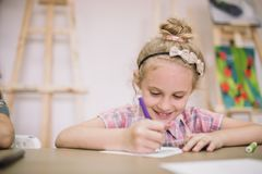 Blonde cute smiling seven-year-old girl, draws at the table in the creative studio.  Royalty Free Stock Photography