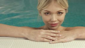 Blonde cute woman enjoying water in swimming pool stock video footage