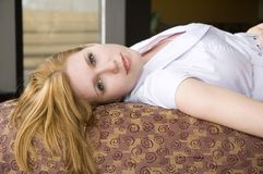 Blonde cutie. Sweet girl laying on a couch Royalty Free Stock Photo