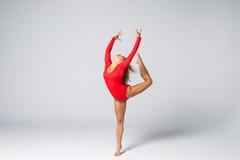 Blonde dünne Frau der jungen Schönheit im roten Körper, der gymnastische Übungen auf weißem Hintergrund springt und tut Stockfotografie