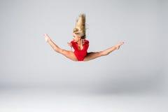 Blonde dünne Frau der jungen Schönheit im roten Körper, der gymnastische Übungen auf weißem Hintergrund springt und tut Lizenzfreie Stockfotografie