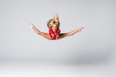 Blonde dünne Frau der jungen Schönheit im roten Körper, der gymnastische Übungen auf weißem Hintergrund springt und tut Lizenzfreie Stockbilder