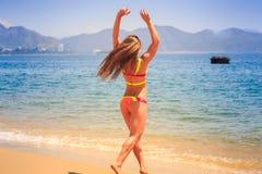 blonde dünne Mädchenrückseite im Bikini geht in Meer gegen Hügel Lizenzfreie Stockfotos