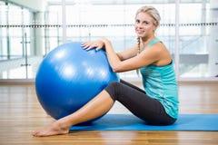 Blonde d'ajustement sur le tapis posant avec la boule de forme physique image libre de droits